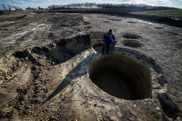 Wilhelm Gábor vezető régész egy kút maradványát mutatja a kecskeméti feltáráson / fotó: MTI - Ujvári Sándor